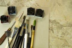 艺术工具,刷子,丙烯酸酯在一个灰色册页为画 免版税图库摄影