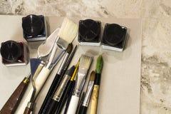艺术工具,刷子,丙烯酸酯在一个灰色册页为画 免版税库存照片