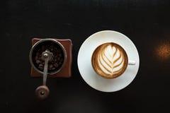 艺术拿铁热的咖啡平的位置安置与手动压榨机一起的 免版税库存照片