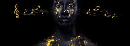 艺术时尚构成 有黑构成的惊人的美国黑人的妇女和漏的金油漆和笔记 在身体的五颜六色的艺术 库存照片
