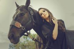 艺术时尚美丽的妇女和马 免版税库存照片