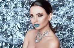 艺术秀丽方式高关键构成理想的冬天 有蓝色雪嘴唇的美丽的时装模特儿女孩 在闪烁发光的背景和精采首饰的假日构成 免版税库存照片