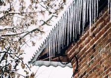 艺术秀丽方式高关键构成理想的冬天 老砖房子和冰柱 库存图片