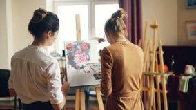 艺术系学生绘的花后面看法在附近站立和检查她的工作的帆布和她有用的老师的 股票视频