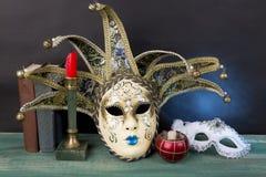 艺术背景黑色概念屏蔽油漆红色地点白色 与葡萄酒书和cand的威尼斯式狂欢节面具 库存图片