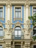 艺术装饰样式装饰了与拿着月桂树花圈的妇女雕象的窗口  免版税图库摄影