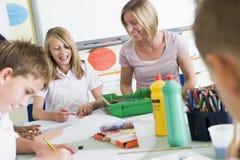 艺术课他们学童的教师 免版税库存照片