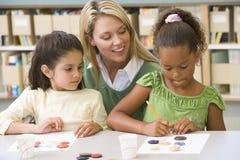 艺术课坐的实习教师 免版税库存照片