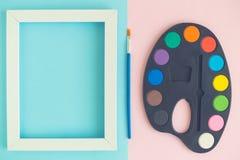 艺术调色板平的位置有油漆、刷子和图象框架的 库存图片
