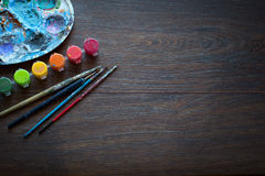 艺术集合,调色板,油漆,在木背景的刷子 免版税库存图片
