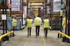 艾塞克斯,英国2016年3月13日:反射性背心的职员轻易地胜过照相机的在超级市场配给物仓库里 免版税库存图片
