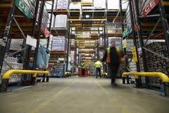 艾塞克斯,英国2016年3月13日:在存储单元之间的一个走道在超级市场配给物仓库里 免版税库存照片