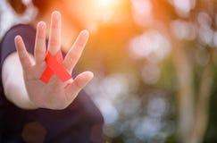 艾滋病意识活动 举行红色艾滋病了悟的女性手 免版税库存图片