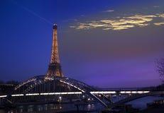 艾菲尔铁塔在2012年3月17日照亮了和桥梁Passerelle Debilly,从塞纳河码头的看法在巴黎,法国 免版税库存照片