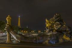 艾菲尔铁塔视图和一个雕象从Pont亚历山大III在晚上 免版税库存图片