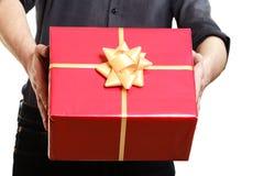 节假日 供以人员给有金黄ribbo的红色礼物盒 免版税库存图片