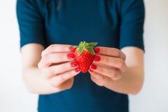细节射击了有拿着一个可口红色草莓的红色钉子的妇女的手 免版税库存照片