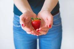 细节射击了有拿着一个可口草莓,白色背景的红色钉子的妇女的手 免版税图库摄影