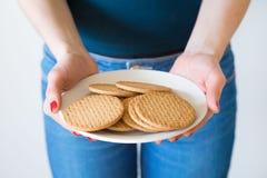 细节射击了有拿着简单的可口曲奇饼的板材红色钉子的妇女的手,白色背景 库存图片