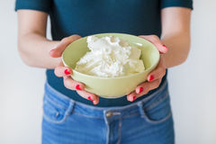 细节射击了有相当拿着碗的红色钉子的妇女的手有很多健康酸奶干酪,白色背景 库存图片