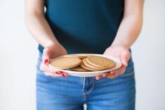细节射击了有相当拿着简单的曲奇饼的板材红色钉子的妇女的手,白色背景 免版税库存照片