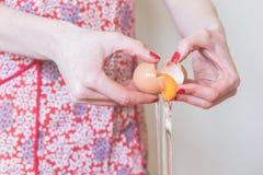 细节射击了崩裂鸡蛋的妇女的手 库存照片