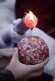 细节拿着在圣周期间,在手上抱一个孩子的球的悔罪者红色蜡烛倾吐的蜡 免版税库存图片