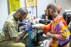 节日参加者在克拉科夫的国会商展中心做纹身花刺在第11次国际纹身花刺大会 库存图片