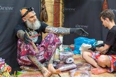 节日参加者在克拉科夫的国会商展中心做纹身花刺在第11次国际纹身花刺大会 免版税图库摄影