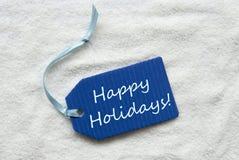 节日快乐在蓝色标签沙子背景 库存图片
