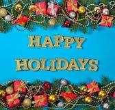 节日快乐金黄文本和云杉的分支和圣诞节装饰 免版税库存图片
