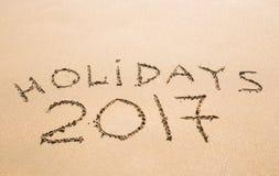 节日快乐2017年 写在沙子在海滩 假日,圣诞节,新年2017年概念 库存图片