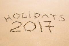 节日快乐2017年 写在沙子在海滩 假日,圣诞节,新年2017年概念 免版税库存照片