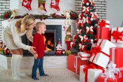 节日快乐!逗人喜爱的小孩发现了许多礼物在圣诞树下 免版税图库摄影