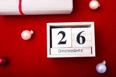 节礼日销售 日历与在红色背景的日期 圣诞节概念 12月26日 圣诞节球和礼物 顶视图 复制sp 免版税库存照片