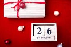 节礼日销售 日历与在红色背景的日期 圣诞节概念 12月26日 圣诞节球和礼物 顶视图 复制sp 库存图片