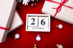 节礼日销售 日历与在红色背景的日期 圣诞节概念 12月26日 圣诞节球和礼物 顶视图 复制sp 库存照片
