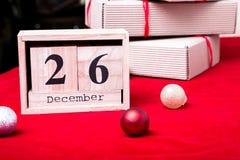 节礼日销售 日历与在红色背景的日期 圣诞节概念 12月26日 圣诞节球和礼物 库存图片