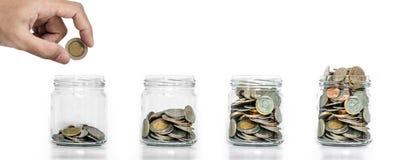 节约金钱,把硬币放的手在有硬币的玻璃瓶子在长大里面,在白色背景上 免版税库存图片