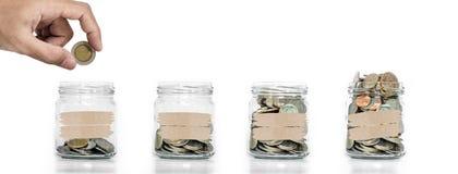 节约金钱,把硬币放的手在有硬币的玻璃瓶子在长大里面,在白色背景上 库存照片