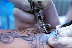 细节纹身花刺做-墨水、机器和手在手套 库存图片