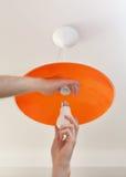 节能LED电灯泡在人的手,灯的替换上在天花板发光设备的由橙色磨玻璃制成 库存照片