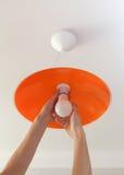 节能LED电灯泡在人的手,灯的替换上在天花板发光设备的由橙色磨玻璃制成 免版税库存照片