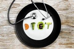 节食与一个听诊器的文本在板材 库存照片