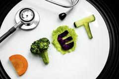 节食与一个听诊器的词在板材 库存图片