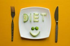 节食和一张微笑的面孔由黄瓜制成 免版税库存图片