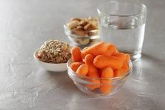 节食的分类健康快餐:嫩胡萝卜、坚果、格兰诺拉麦片棒和杯在桌上的水 免版税库存图片
