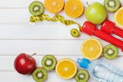 节食计划、菜单或者节目、卷尺、水、哑铃和新鲜水果饮食食物在白色背景,戒毒所概念的 免版税库存图片