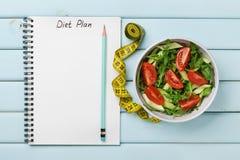 节食计划、菜单或者节目、卷尺、水和新鲜的沙拉饮食食物在蓝色背景的,减重和戒毒所概念 免版税图库摄影