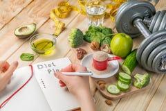节食计划概念-绿色食物和笔记本的选择 库存照片